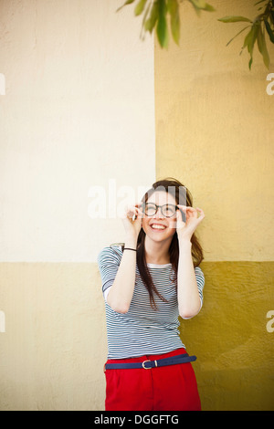 Portrait of young woman in front of color divided wall - Stock Photo