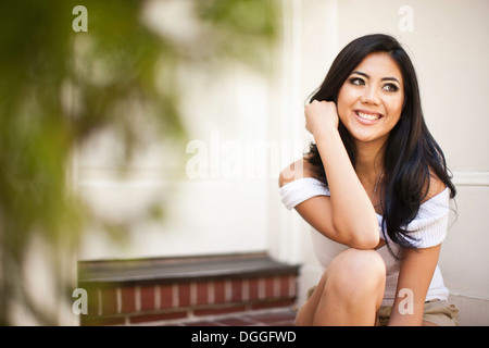 Portrait of young woman on front door steps - Stock Photo