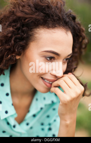 Young woman smiling with hand on chin, close up - Stock Photo