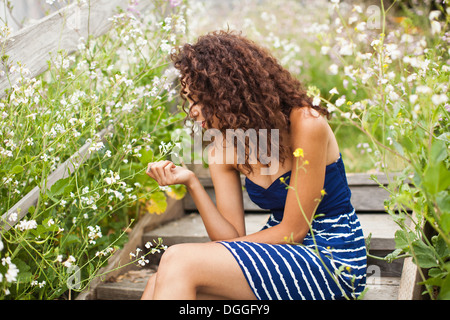 Young woman sitting on wooden steps looking at flower - Stock Photo
