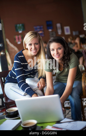 Two teenage girls using computer in cafe - Stock Photo