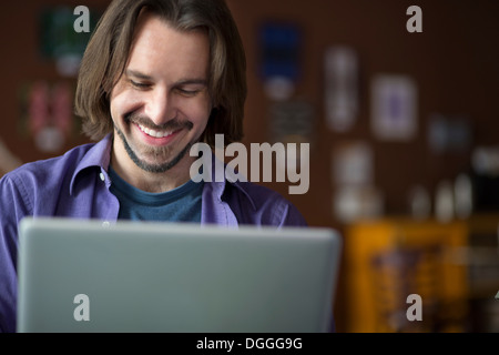Portrait of young man using at computer in cafe - Stock Photo