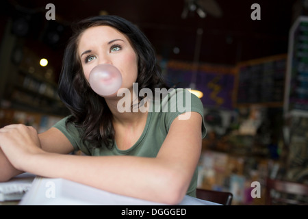 Portrait of teenage girl blowing bubblegum in coffee house - Stock Photo