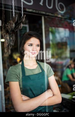 Portrait of teenage girl through cafe window - Stock Photo
