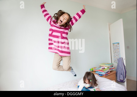 Girl jumping on bed and pulling face - Stock Photo