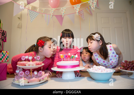 Girls blowing out birthday candles on cake - Stock Photo
