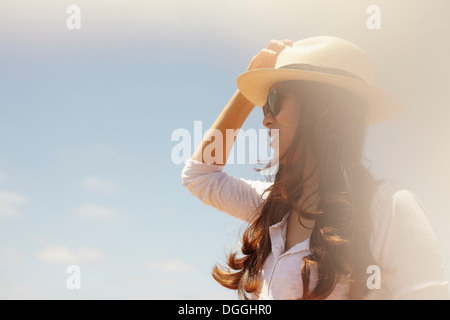 Young woman wearing sunhat and sunglasses