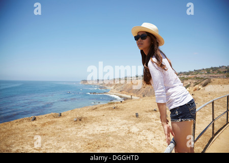 Young woman standing on fence, Palos Verdes, California, USA - Stock Photo
