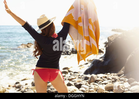 Young woman holding up towel, Palos Verdes, California, USA - Stock Photo