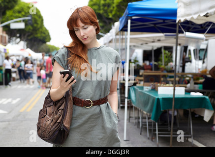 Mid adult woman looking at mobile phone in city - Stock Photo