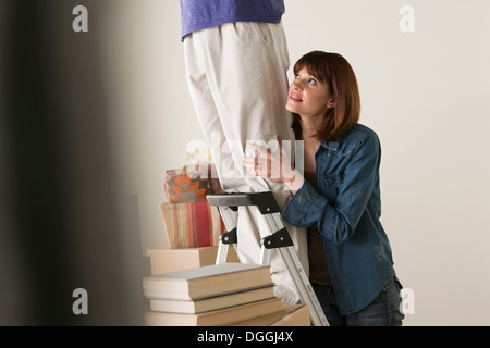 Woman holding onto man on stepladder - Stock Photo
