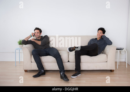 Two male office workers relaxing with mobiles on sofa - Stock Photo