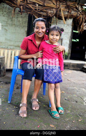 Young mother with her daughter standing in front of her house, La Sabanita, Masaya, Nicaragua, Central America - Stock Photo