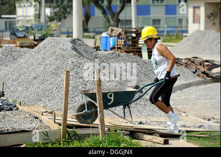 Woman pushing a wheelbarrow on a building site of the 'Esperanca' housing co-operative, each family helping out - Stock Photo