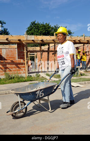 Woman from the slums, favelas, pushing a wheelbarrow on a building site of the 'Esperanca' housing co-operative, - Stock Photo