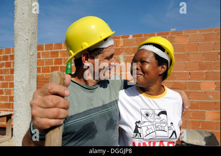 Couple in love, man and woman, 50 years, looking at each other, they are working together on a building site of - Stock Photo