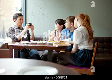 Four friends in restaurant, young man taking photo - Stock Photo