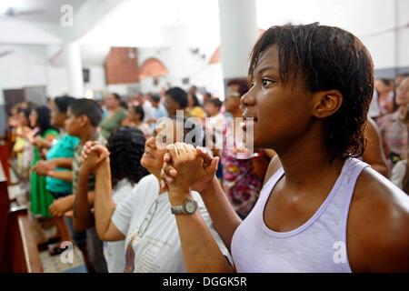 Worshippers holding each other's hands and praying, Catholic mass in a slum or favela, Jacarezinho favela, Rio de - Stock Photo