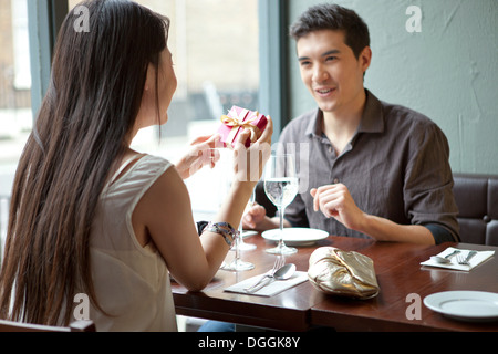 Young couple in restaurant, woman holding gift box - Stock Photo