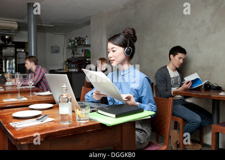 Young woman with laptop in cafe - Stock Photo