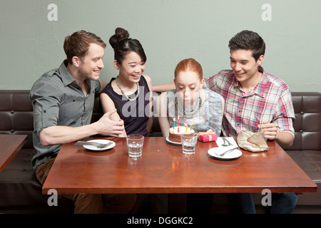 Four friends celebrating birthday in restaurant - Stock Photo