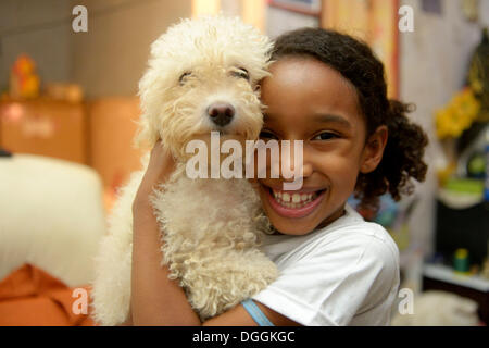 Girl with a poodle in a slum or favela, Jacarezinho favela, Rio de Janeiro, Rio de Janeiro State, Brazil - Stock Photo