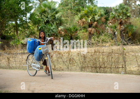 Girl transporting two canisters with water from the reservoir of the nearby pagoda on her bike to her home, Trapang - Stock Photo