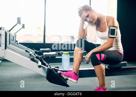 Young woman taking a break from exercising in gym - Stock Photo