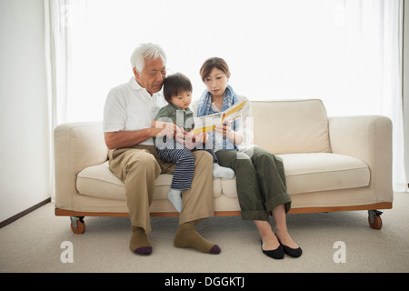 Mother reading to son sitting on grandfather's lap - Stock Photo