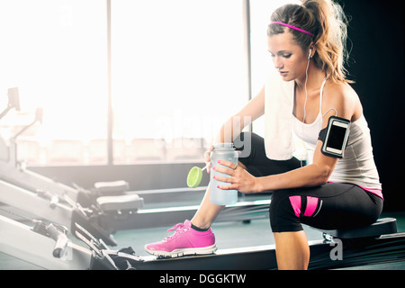 Young woman holding water bottle in gym - Stock Photo