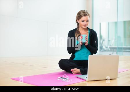 Young woman on yoga mat with mug of tea - Stock Photo