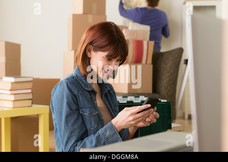 Woman looking at cellphone whilst moving house - Stock Photo
