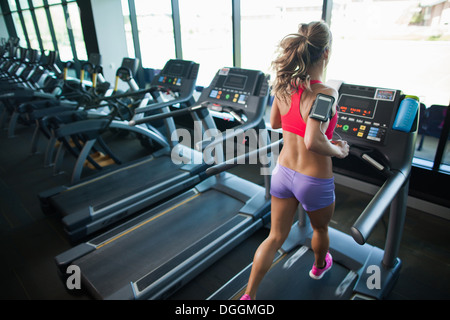 Young woman running on treadmill in gym - Stock Photo
