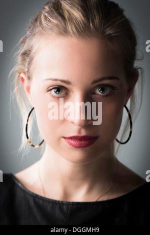 Young woman wearing hoop earrings, portrait - Stock Photo