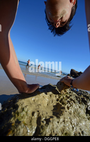 People apply muds on Bolonia beach, Tarifa - Stock Photo
