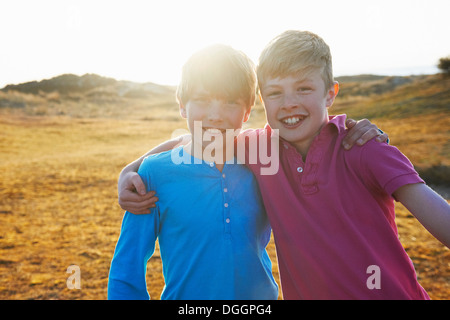 Two boys with arms around each other - Stock Photo