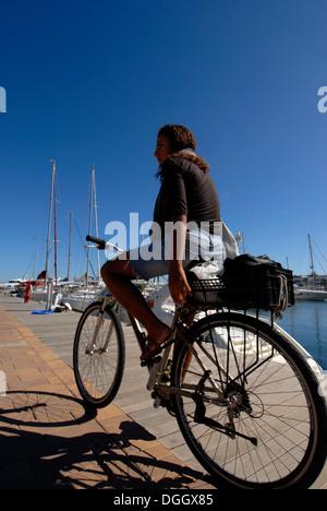 Young brazilian woman in her bike, La Savina, Formentera - Stock Photo