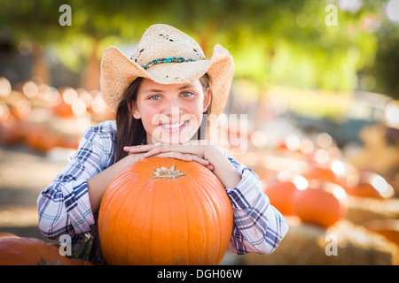 Portrait of Preteen Girl Wearing Cowboy Hat Playing at the Pumpkin Patch in a Rustic Country Setting. - Stock Photo