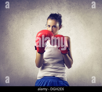 Portrait of a girl boxer in fighting stance - Stock Photo