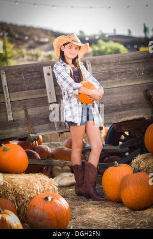 Preteen Girl Wearing Cowboy Hat Portrait at the Pumpkin Patch in a Rustic Setting. - Stock Photo