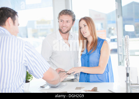 Young couple talking with salesman in kitchen showroom - Stock Photo
