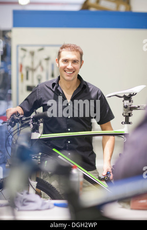 Mid adult man in repair shop with bicycle - Stock Photo