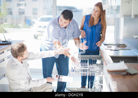 Couple and salesman looking at dishwasher in kitchen showroom - Stock Photo