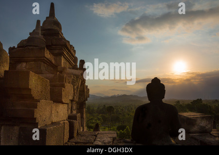 Sun setting in late afternoon shining its golden light on Borobudur, Central Java, Indonesia. - Stock Photo