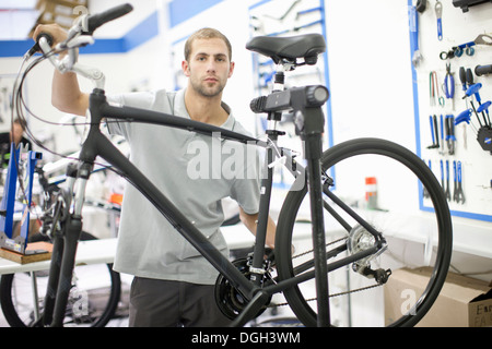 Young man in repair shop with bicycle - Stock Photo