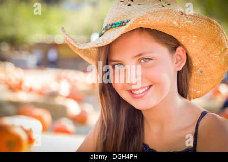 Preteen Girl Portrait Wearing Cowboy Hat at Pumpkin Patch in Rustic Setting. - Stock Photo