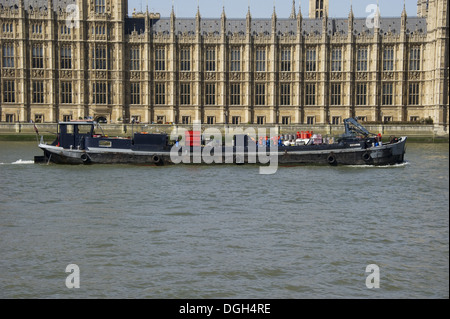 Barge on river beside Palace of Westminster (Houses of Parliament), River Thames, Westminster, London, England, - Stock Photo