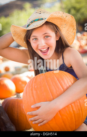Preteen Girl Holding A Large Pumpkin at the Pumpkin Patch in a Rustic Setting. - Stock Photo