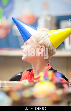 Boy at birthday party wearing two party hats - Stock Photo