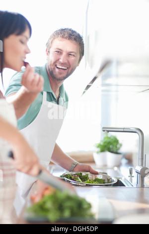 Couple preparing food, man feeding woman - Stock Photo